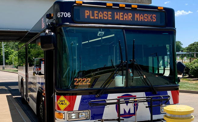 A MetroBus on the street with the notification saying Please Wear Masks
