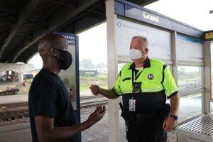 Security personnel talking to a passenger on a MetroLink platform.