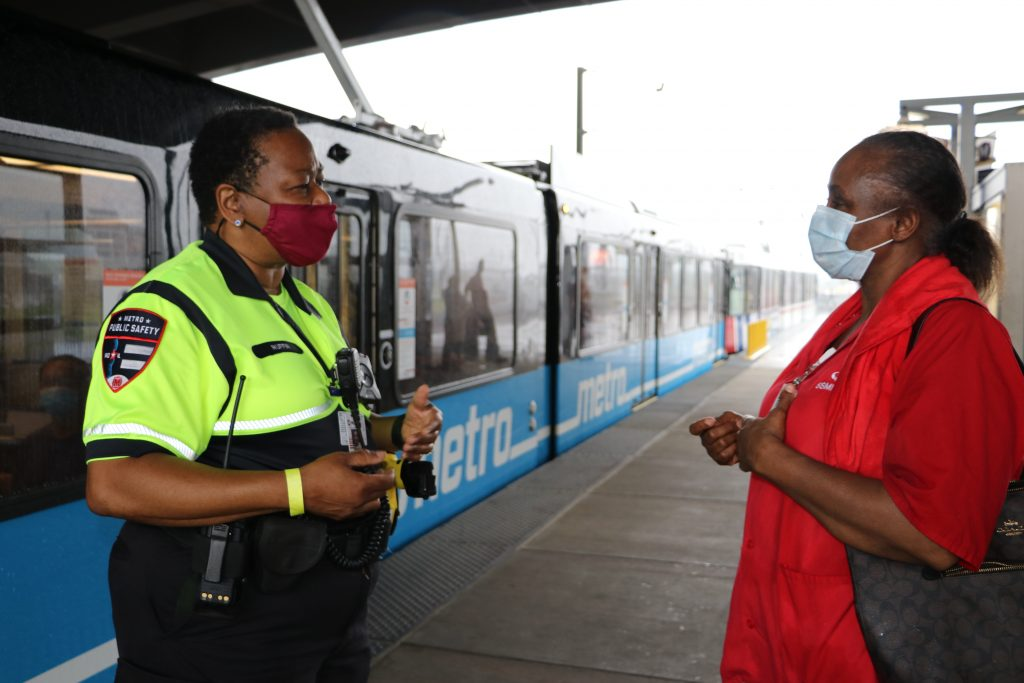 Security personnel talking to a passenger on a MetroLink platform with a blue train passing behind it.