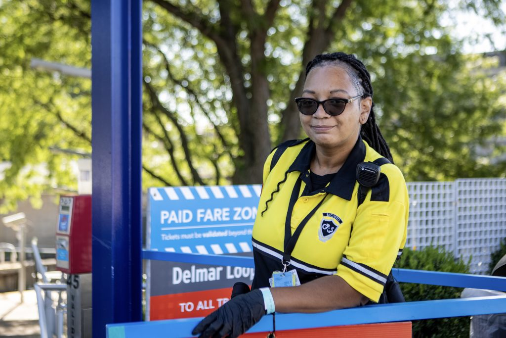 LaAndrea, fare enforcement team member, standing at the entrance to the Delmar Loop MetroLink Station smiling