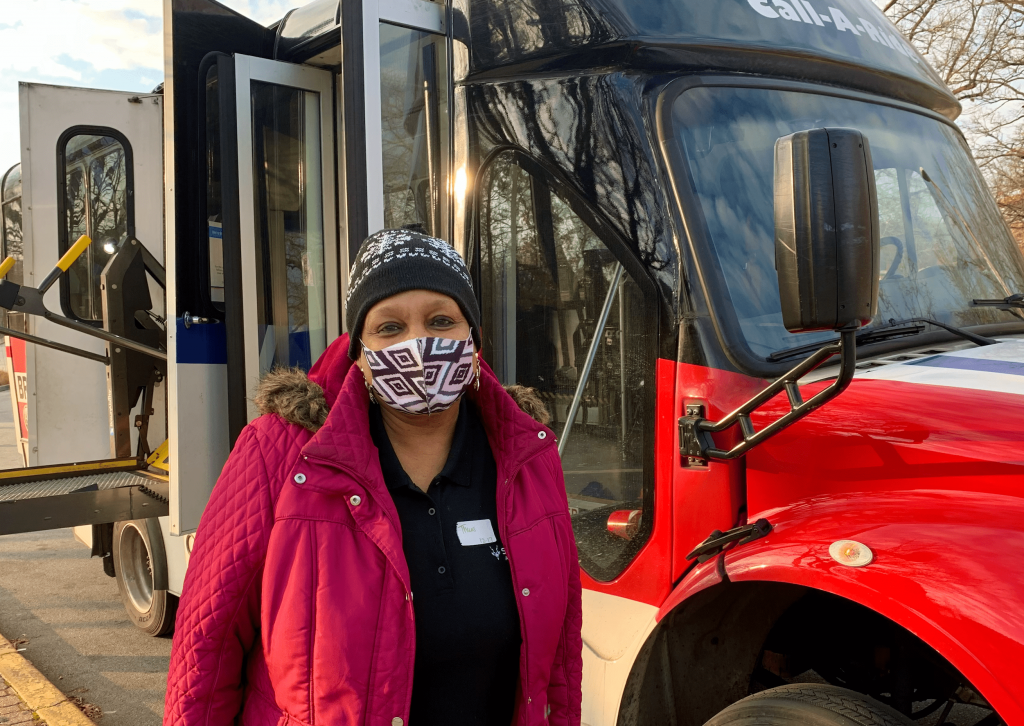 Image of passenger Joyce, smiling and standing in front of a Metro Call-A-Ride van