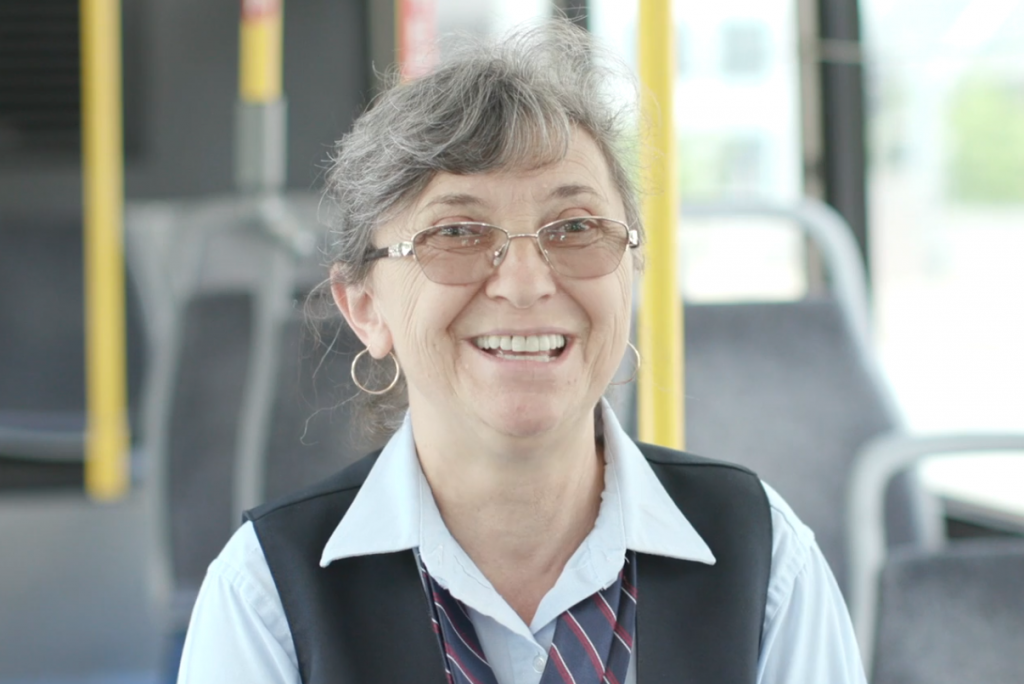 Photo of MetroBus Operator Violeta sitting on a bus and smiling at the camera