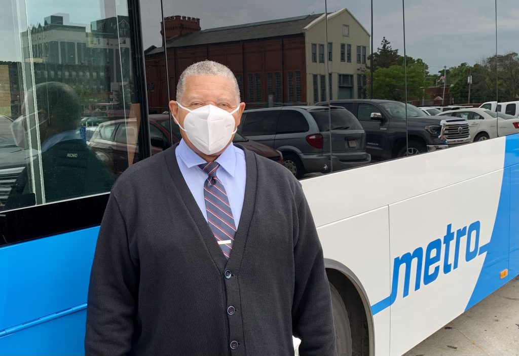 Image of MetroBus Operator Orvin standing in front of a bus and wearing a mask