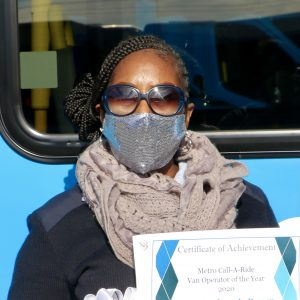 Metro Call-A-Ride 2020 Operator of the Year Barbara, smiling at the camera and holding her certificate of achievement