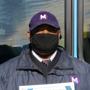 Metro Call-A-Ride 2020 Operator of the Year Howell, smiling at the camera and holding his certificate of achievement