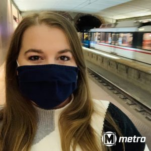 Selfie of a woman wearing a mask on the 8th and Pine MetroLink platform with a train driving past in the background. Metro logo on the bottom right