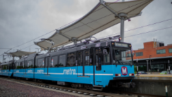 A MetroLink train stops at the Cortex MetroLink station. The platform canopies appear in the background.