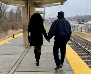 Passenger Profile: Lawanda and Jose walking away from the camera on the Fairview Heights MetroLink platform, holding hands