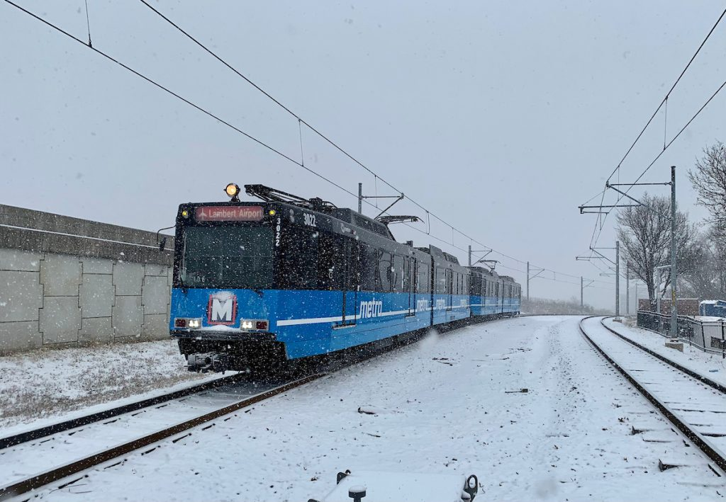 Front of a west-bound MetroLink train arriving at the North Hanley station. It is snowing and snow covers the ground and tracks.