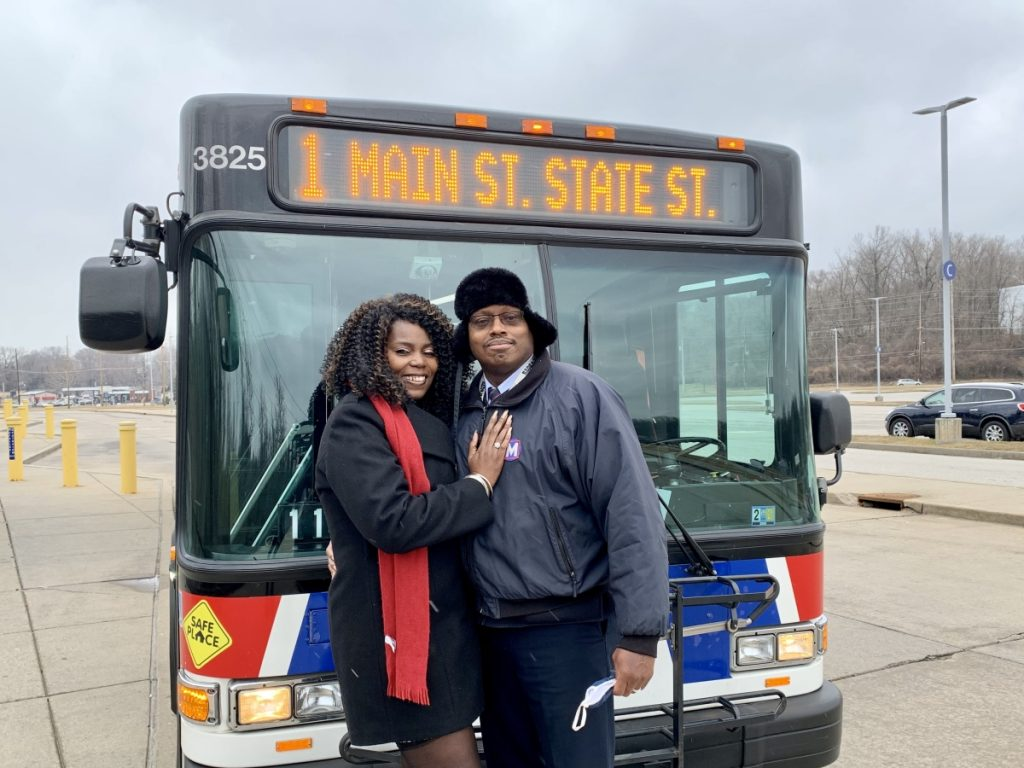 "Passenger Profile: Lawanda and Jose standing in front of a MetroBus with a headsign that reads ""1 Main St State St"""