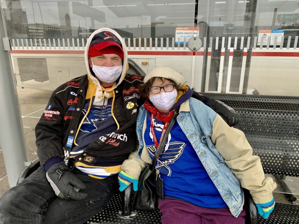 Passengers Tom and Carol sitting at the #10 bus stop at the Civic Center Transit Center. They are both sitting on the bench, smiling at the camera and wearing face masks