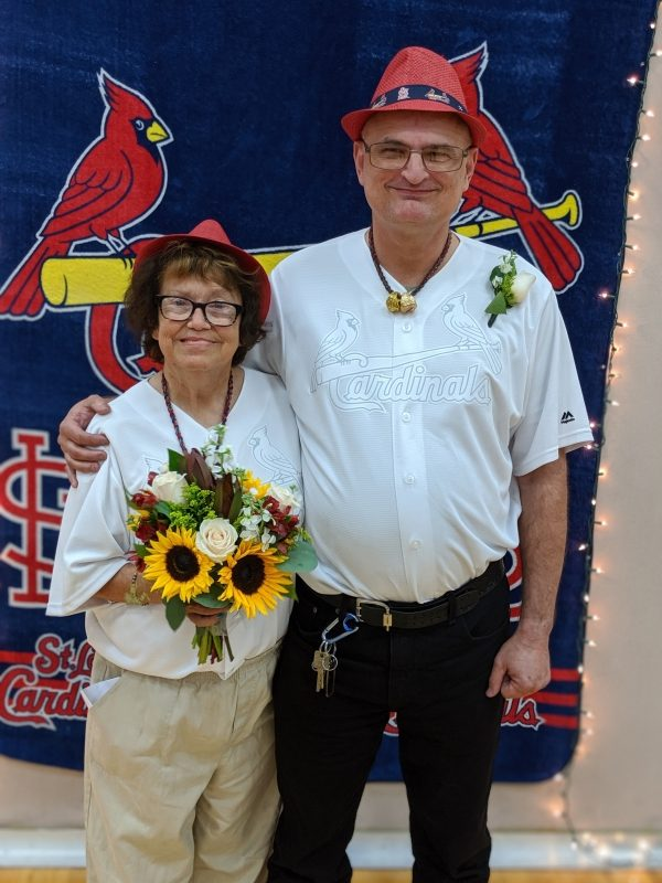 Photo of passenger Tom and Carol on their wedding day, smiling at the camera. Tom's arm is around Carol, and they are wearing matching white Cardinals jerseys. Carol is holding a yellow and purple bridal bouquet.