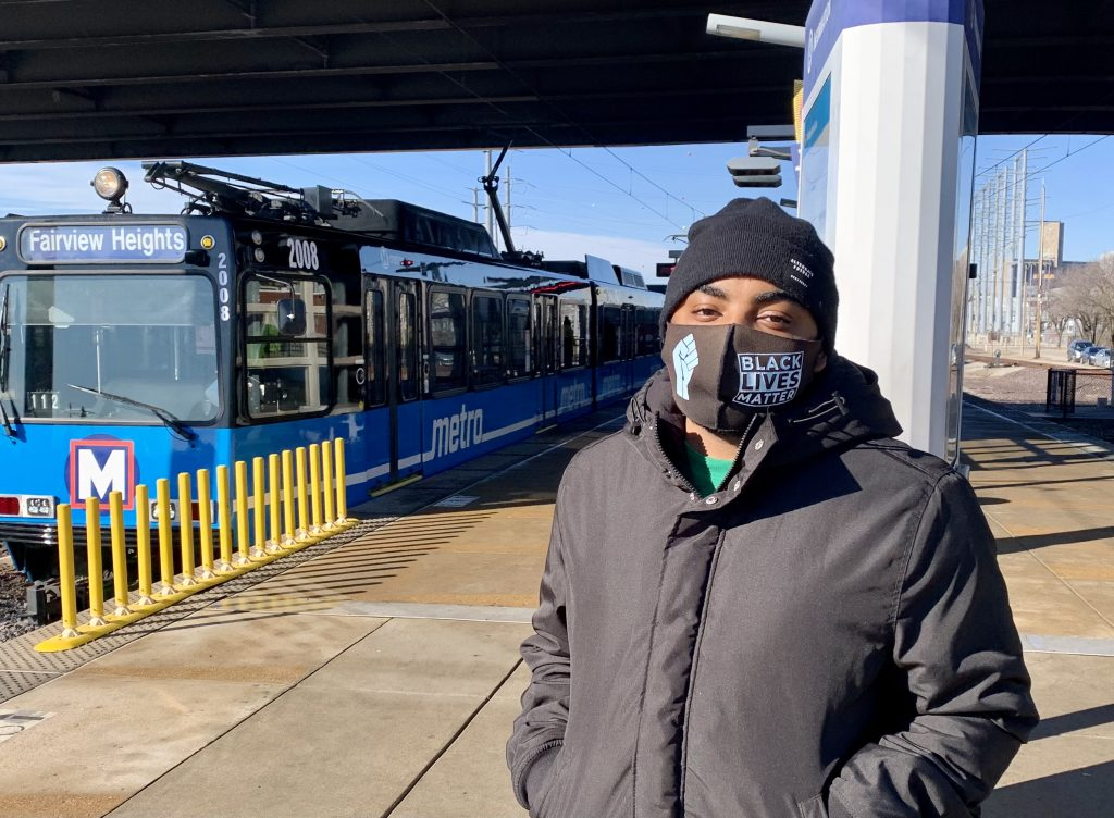 Passenger Robert standing on the Grand MetroLink Station platform looking at the camera, with a blue MetroLink train behind him
