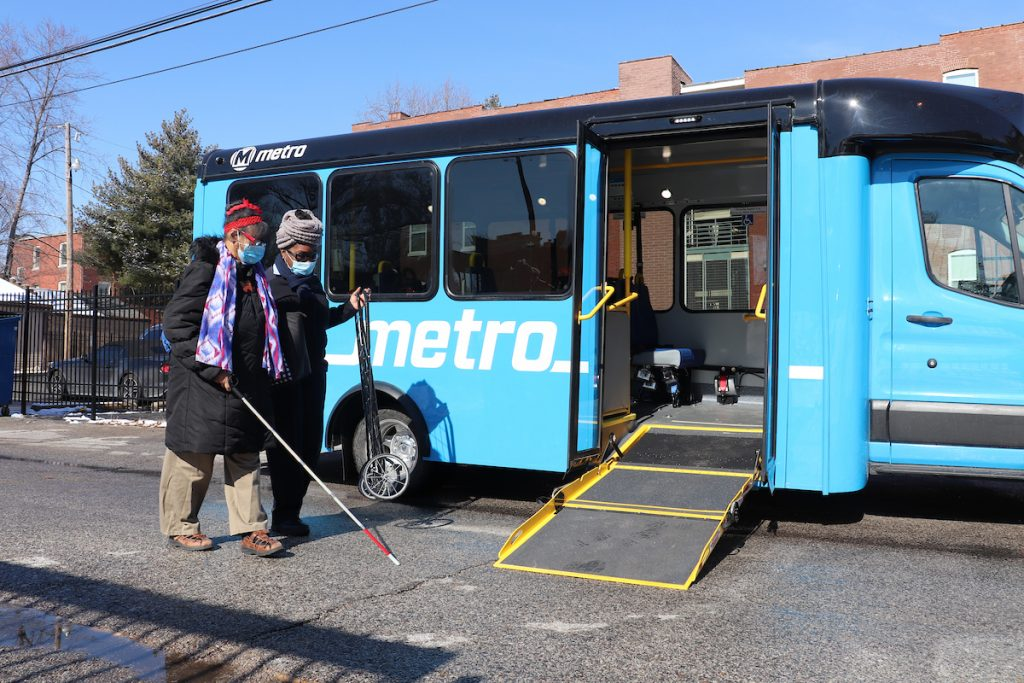 Call-A-Ride operator, Barbara, helps rider, Donna, on board a Call-A-Ride van. The doors are open and the ramp is lowered. Red brick buildings appear in the background.