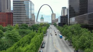 Aerial shot of a MetroBus driving down Market street downtown. Trees line market street and the Old Courthouse and Gateway Arch appear in the background.