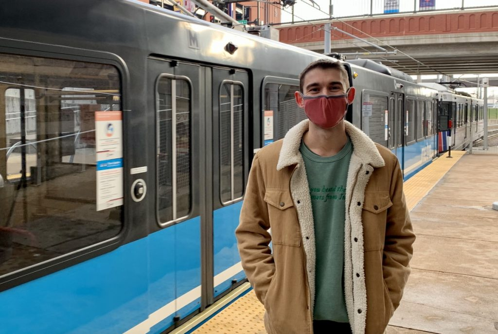 Image of passenger Kevin on the platform at Stadium Station, wearing a red mask and looking at the camera with a blue MetroLink train behind him