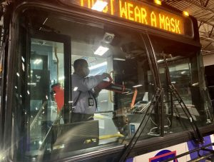 Employee cleaning the interior of a bus with new disinfecting technology. The photo was taken from the outside of the bus, looking in.