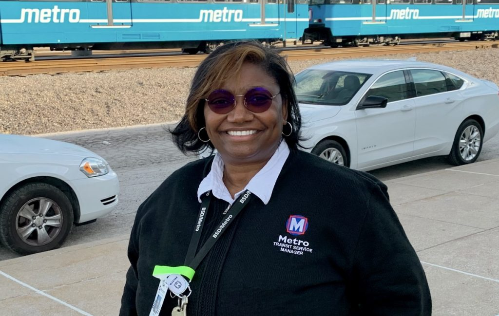 Team member Edith standing outside of a Metro facility, smiling at the camera and wearing glasses. There are two white cars behind her, and in the background is a blue MetroLink train