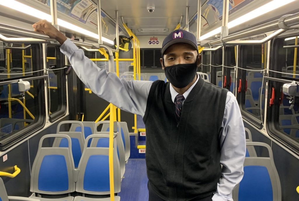 MetroBus Operator E'Quain standing on a bus looking at the camera and wearing a mask