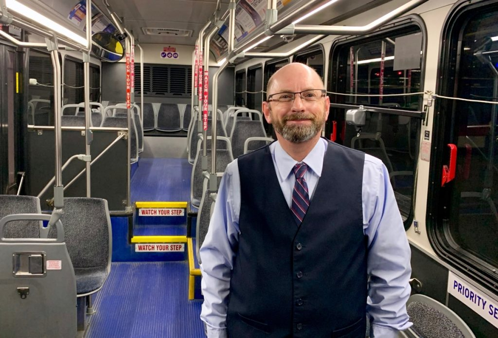 MetroBus Operator Ken standing on the inside of a bus, smiling at the camera