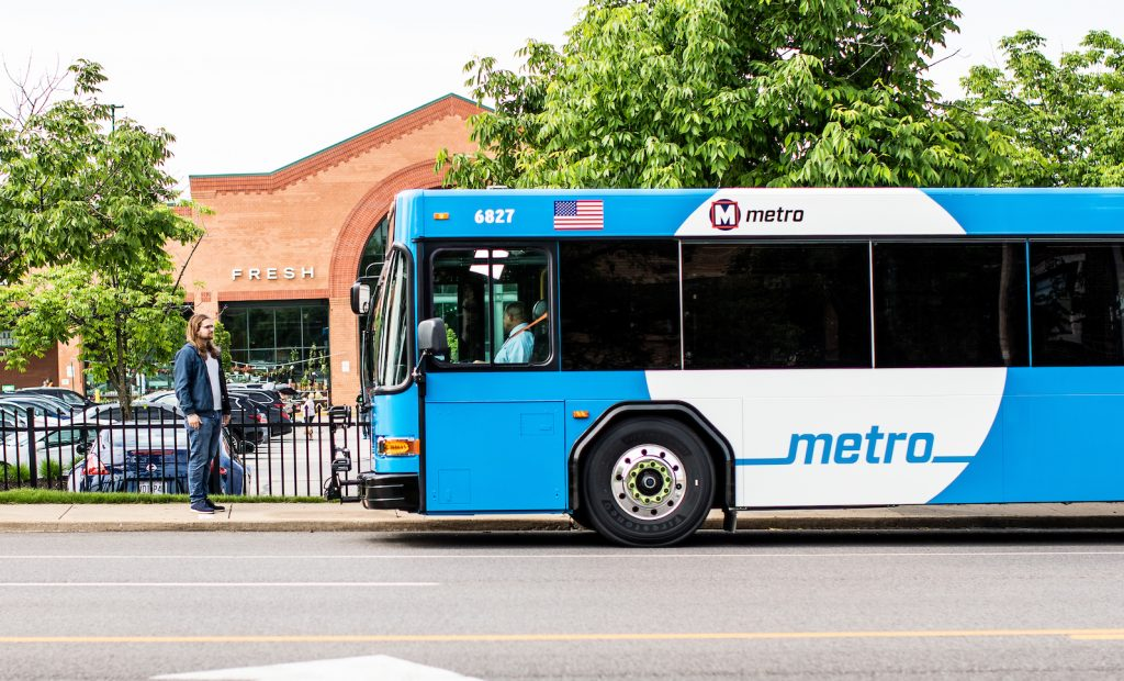 A MetroBus pulls up to a bus stop in front of the Clayton Rd. Schnucks. A rider waits at the bus stop.