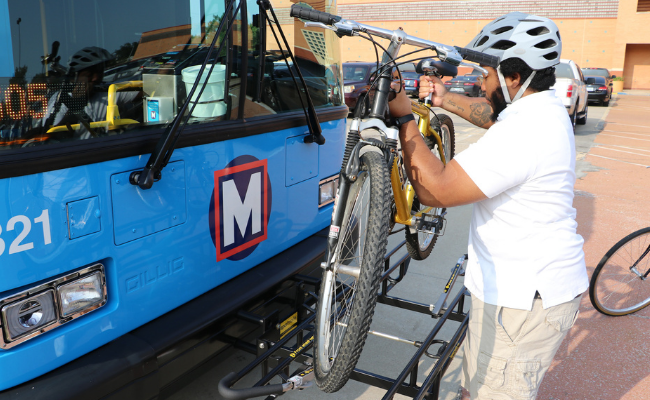 Bring your bike on MetroBus step 2: Man lifting up a bike to place the tires into the bike rack slots.