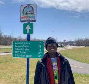 Metro Passenger Dominike standing in front of the MetroBikeLink trail sign at the Fairview Heights MetroLink Station