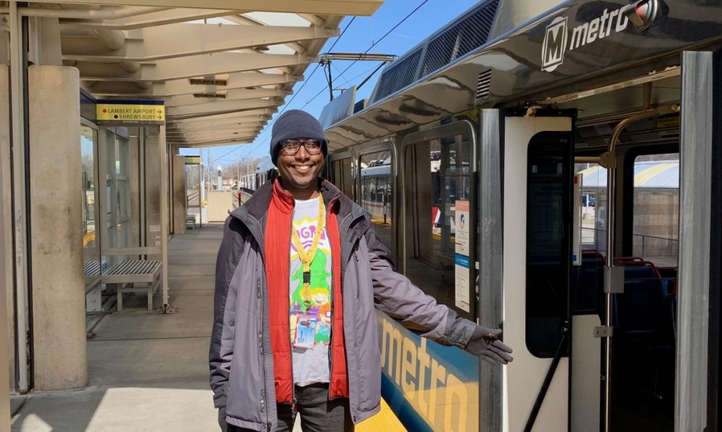 Metro Passenger Dominike standing on the Fairview Heights MetroLink Station platform with a train behind him