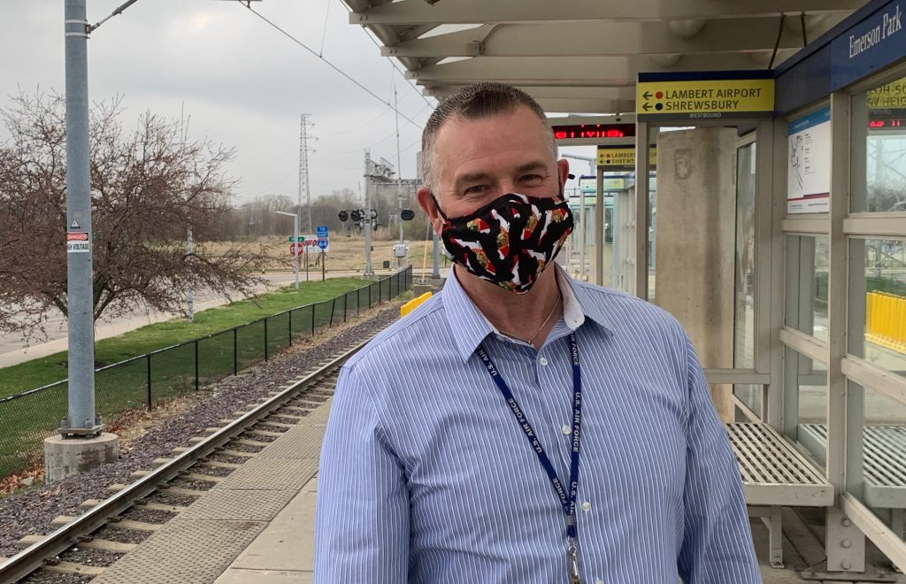 Passenger Doug standing on the Emerson Park MetroLink Station platform, smiling at the camera and wearing a face mask
