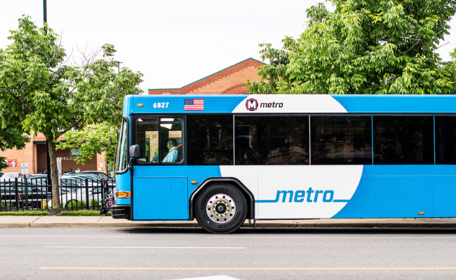 A MetroBus pulls up to a bus stop in front of the Clayton Rd. Schnucks.