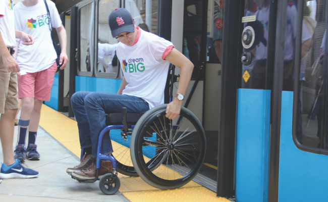 MetroLink passenger exiting a train onto the platform in a wheelchair. Passenger is wearing jeans, a whit shirt and blue baseball cap