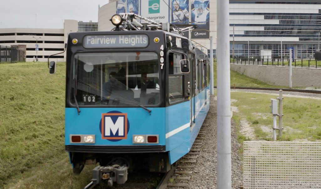 A MetroLink train pulls into the Civic Center MetroLink station. The Enterprise Center appears into the background.