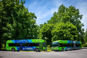 60-foot and 40-foot electric buses on the street with trees behind them