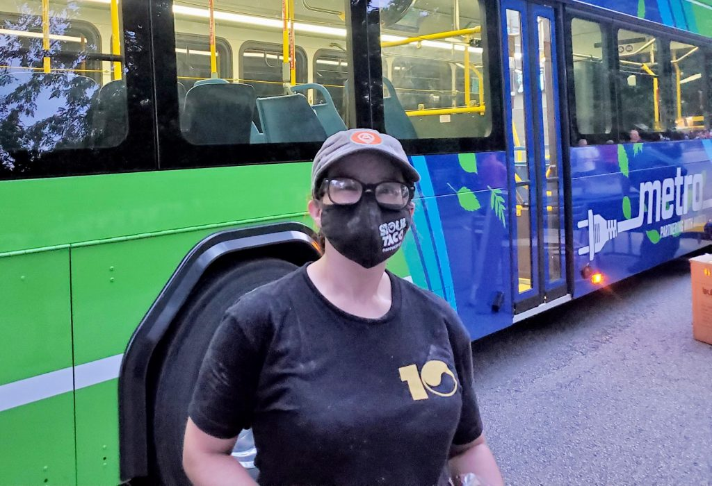 Image of passenger Kayle during the evening standing in front of our new battery electric bus