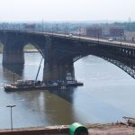 Workers accessing Eads Bridge from a cherry picker on a barge during the rehabilitation project.