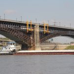 Rehabilitation work continues on Eads Bridge as a barge heads down the Mississippi.