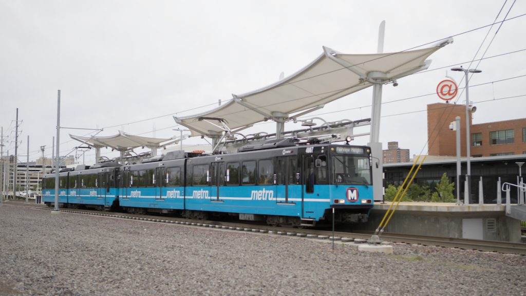 MetroLink train stopped at the Cortex MetroLink station. The canopy of the station and Cortex campus appear in the background.