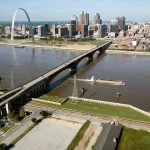 A sweeping view of the historic Eads Bridge with a background that includes the Gateway Arch, downtown St. Louis, and blue skies.
