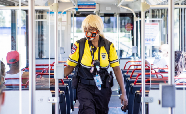 Public Safety team member walking on a MetroLink train, interacting with passengers